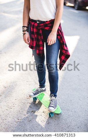 Hipster woman in denim jeans ride her green penny board with blue colored wheels. Depth of field, selective focus - stock photo