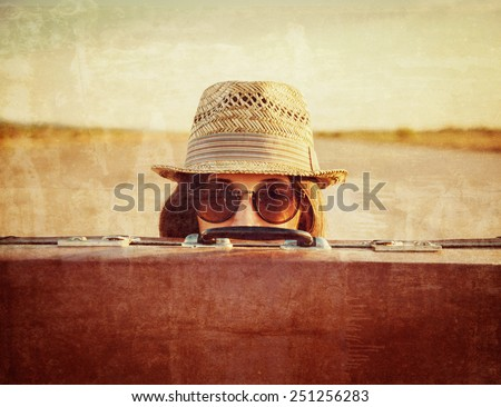 Hipster woman in hat and glasses looks out from vintage suitcase. Vintage image - stock photo