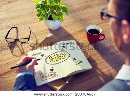 Hipster Writing SEO Concepts on his Note - stock photo