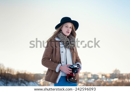 Hipster young girl photographer with old photo camera on a sunny winter day - stock photo