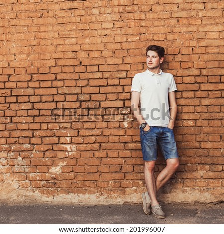 hipster young man on the brick wall - stock photo