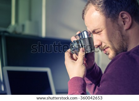 Hipster young man takes a picture with a vintage photo camera  - stock photo