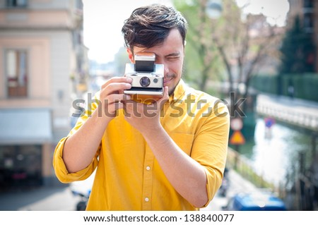 hipster young man with polaroid on the balcony - stock photo