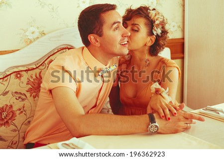 Hipsters' date concept. Portrait of a beautiful kissing couple of hipsters in trendy clothing in vintage cafe. Wedding day. Close up. Indoor shot - stock photo