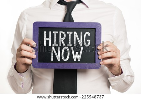 Hiring now Handwritten with white chalk on a blackboard which holding man - stock photo