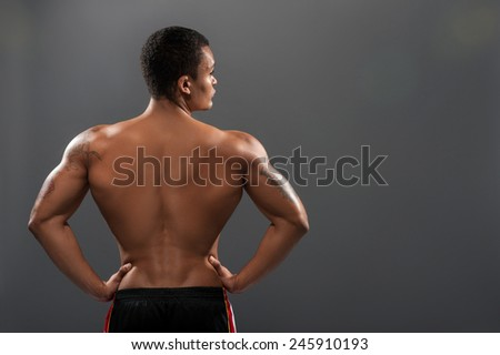 His body is perfect. Rear view of young shirtless African man with muscular body while standing against grey background   - stock photo
