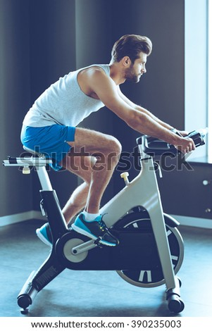 His favorite cardio workout. Side view full length of young handsome man in sportswear cycling at gym - stock photo