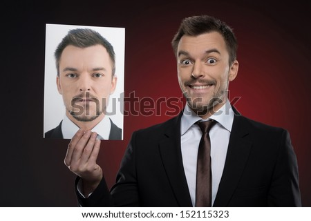 His today mask. Cheerful young man in formalwear holding a photograph of himself while isolated on red - stock photo