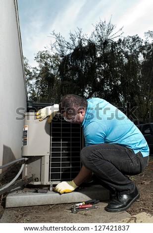 Hispanic air conditioning system repair maintenance man - stock photo
