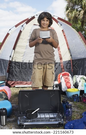 Hispanic boy surrounded by camping supplies - stock photo