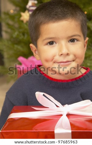 Hispanic boy with Christmas gift - stock photo