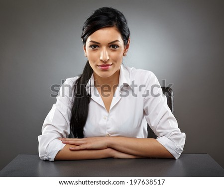 Hispanic business woman sitting at her desk smiling - stock photo