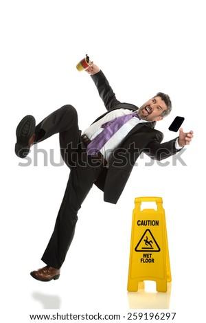 Hispanic businessman falling next to wet floor sign isolated over white background - stock photo