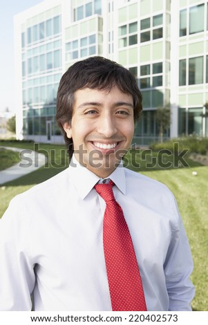 Hispanic businessman in front of office building - stock photo