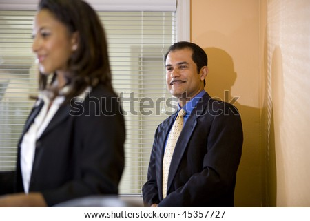 Hispanic businessman looking at young African-American businesswoman in office boardroom - stock photo