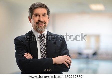 Hispanic businessman with arms crossed inside office building - stock photo