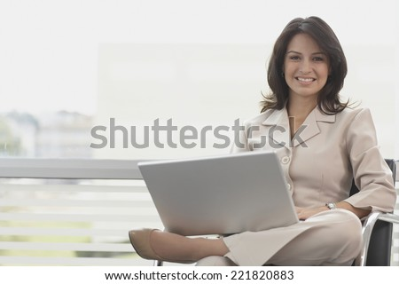 Hispanic businesswoman holding laptop - stock photo