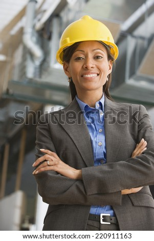 Hispanic businesswoman in hard hat with arms crossed - stock photo
