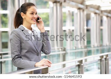 Hispanic Businesswoman Outside Office On Mobile Phone - stock photo