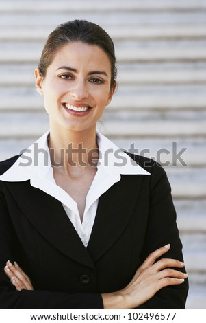 Hispanic businesswoman with arms crossed - stock photo