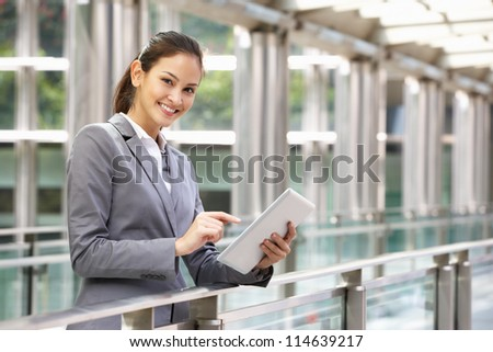 Hispanic Businesswoman Working On Tablet Computer Outside Office - stock photo