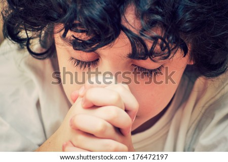 Hispanic child devotedly praying to his Creator in Heaven. Christian worship and relationship. Image has been filtered for effect - stock photo