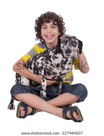 Hispanic child with curly hair petting a female dalmatian dog over white background (not isolated) - stock photo