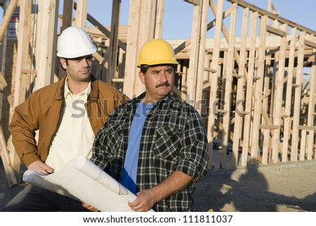 Hispanic construction worker holding blueprints - stock photo