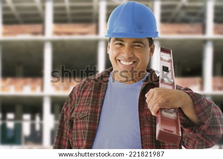 Hispanic construction worker holding level - stock photo