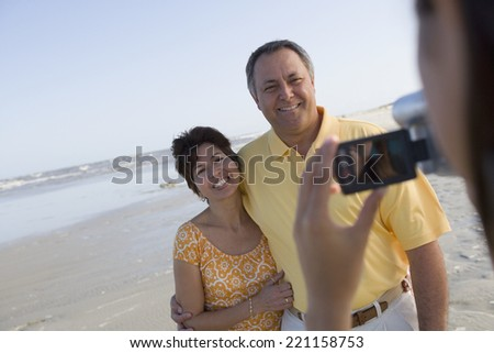 Hispanic couple being video recorded at beach - stock photo