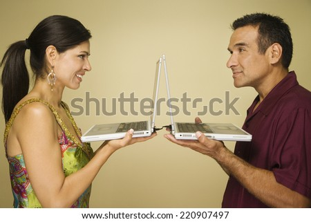 Hispanic couple holding laptops and facing each other - stock photo