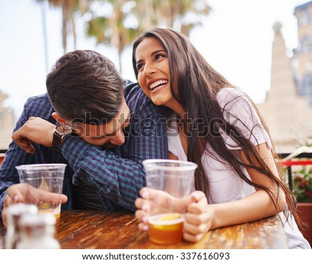 Hispanic couple laughing and having fun while drinking beer shot with selective focus - stock photo