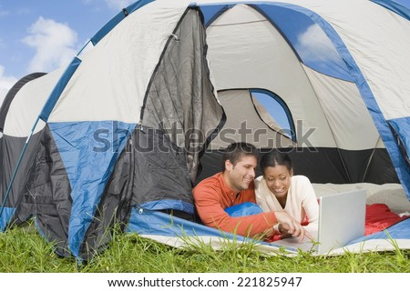 Hispanic couple looking at laptop in tent - stock photo