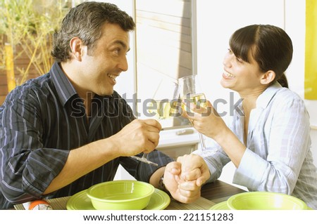 Hispanic couple toasting with wine - stock photo