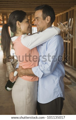 Hispanic couple with champagne on construction site - stock photo