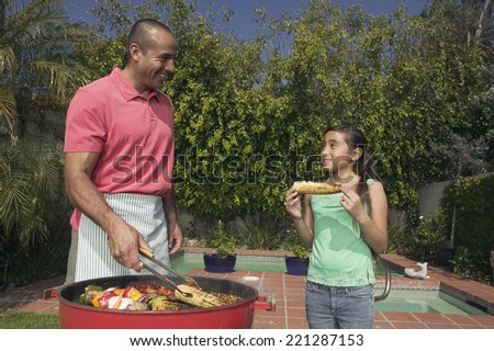 Hispanic father and daughter barbequing - stock photo