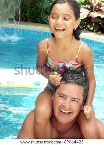 Hispanic father and his daughter enjoying in a swimming pool. - stock photo