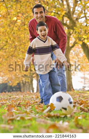 Hispanic father and son playing with soccer ball - stock photo