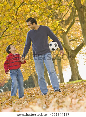 Hispanic father and son with soccer ball in park - stock photo