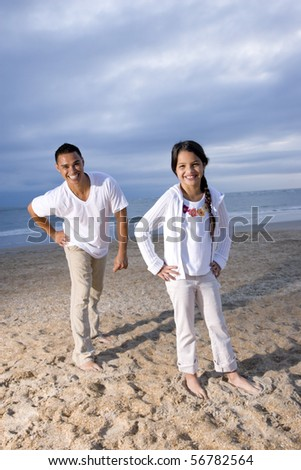 Hispanic father and 9 year old daughter having fun on beach smiling at camera - stock photo