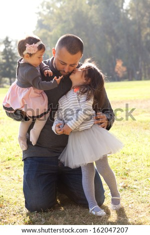 Hispanic father kissing and hugging his two girls - stock photo