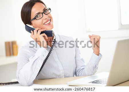 Hispanic female professional with glasses talking on the phone and smiling in the office - stock photo