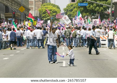 Hispanic girl and father with American flag watch hundreds of thousands of immigrants participating in march for Immigrants and Mexicans protesting Illegal Immigration  Los Angeles, CA, May 1, 2006 - stock photo