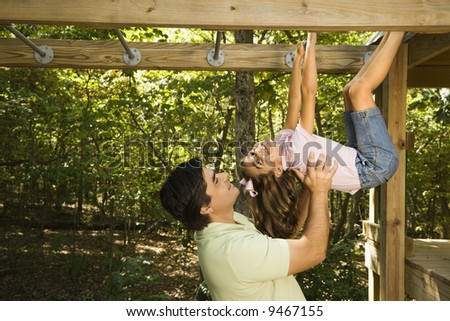 Hispanic girl hanging by arms and legs from monkey bars smiling at father helping her. - stock photo