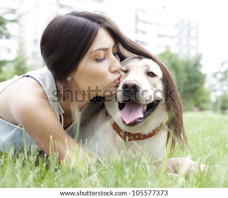 Hispanic girl kissing her dog in the park on the background of the house - stock photo
