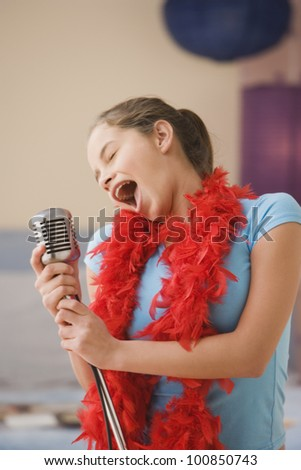 Hispanic girl singing into microphone in bedroom - stock photo