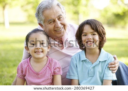 Hispanic Grandmother And Grandfather Relaxing With Grandson In Park - stock photo