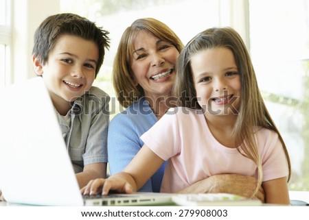 Hispanic Grandmother Using Laptop With Grandchildren - stock photo