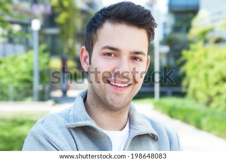 Hispanic guy in a grey jacket laughing at camera - stock photo