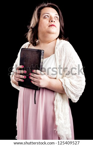 hispanic looking woman in a light dress against a black background holding a bible close to her body as she looks up in thought. - stock photo